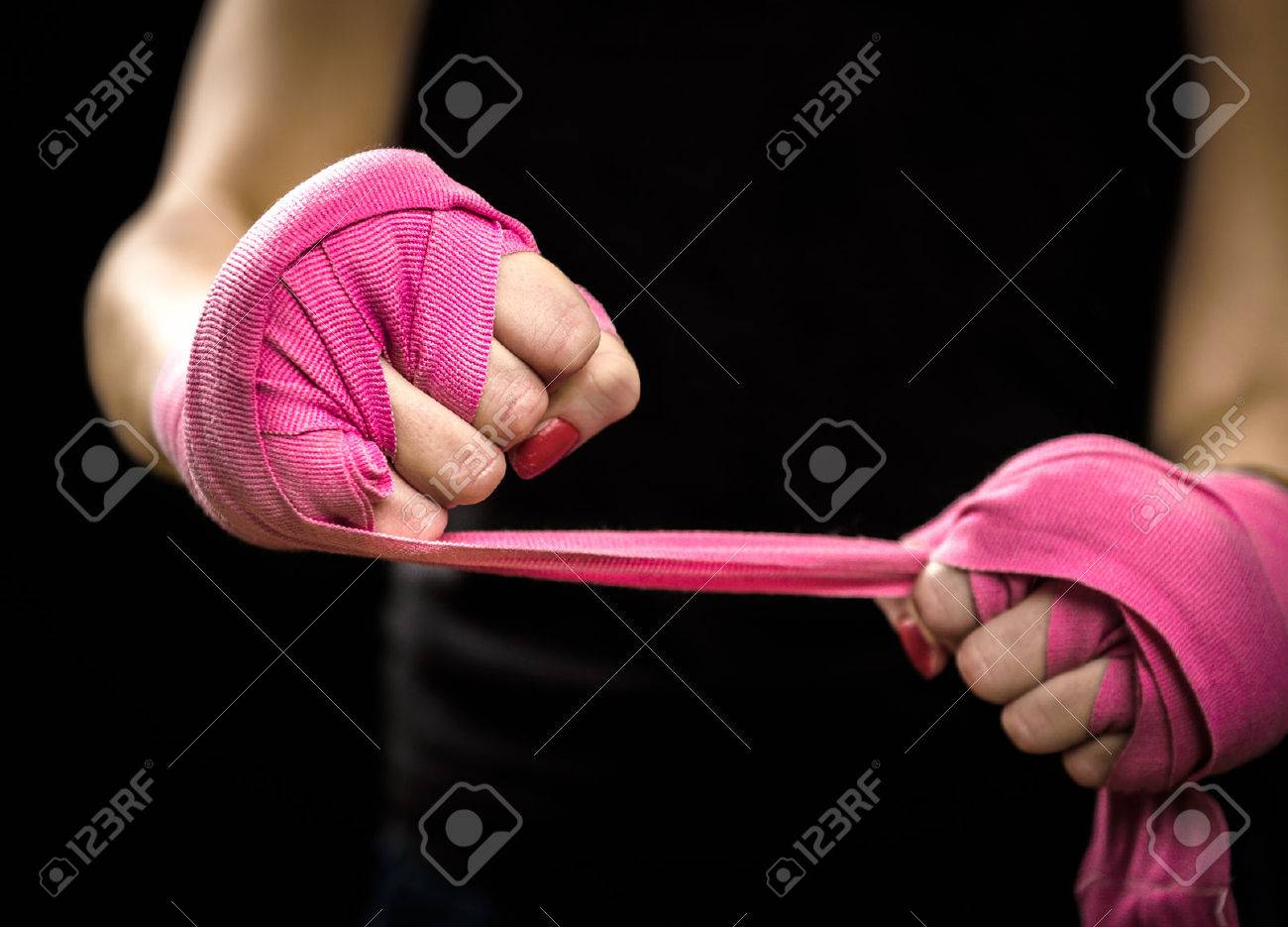 Woman is wrapping hands with pink boxing wraps. Isolated on black with red nails. Strong hand and fist, ready for fight and active exercise - 51071677