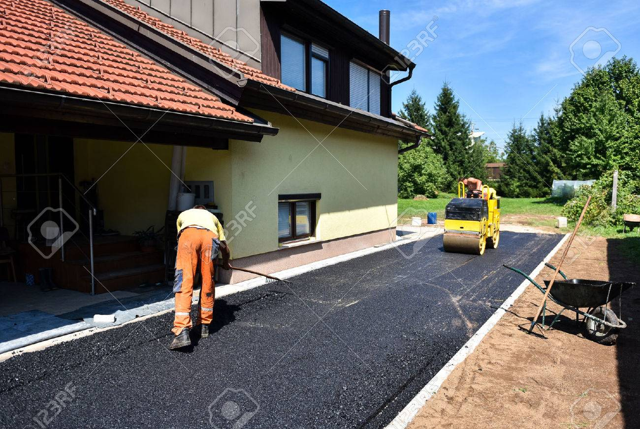 Team of Workers making and constructing asphalt road construction with steamroller. The top layer of asphalt road on a private residence house driveway - 54970832