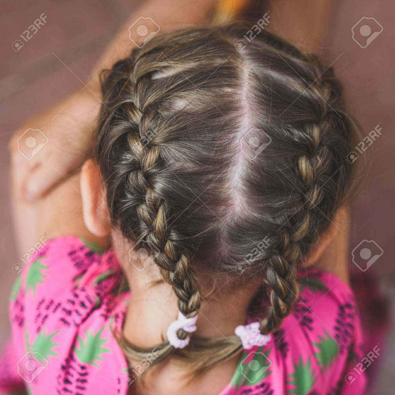 Archivio Fotografico , Trecce sulla testa della bambina. Giovane donna con  i capelli intrecciati è seduto in abito rosa con i capelli fatta in due  trecce