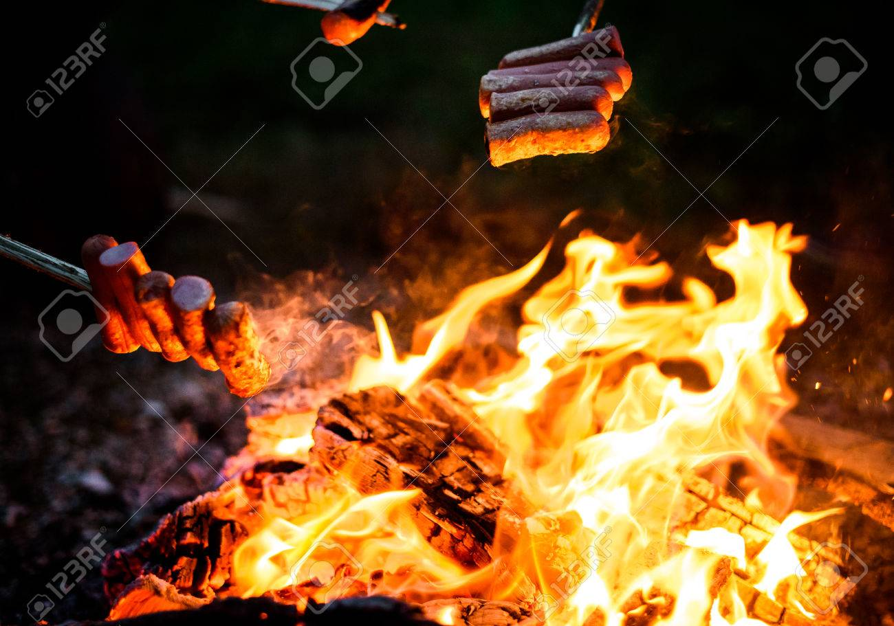 Making And Cooking Hot Dog Sausages Over Open Camp Fire Grilling Food Flames Of