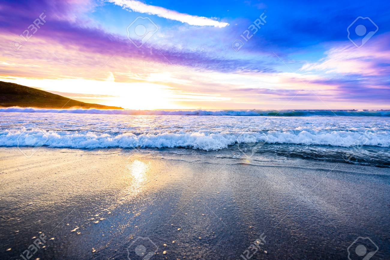 Small ocean sea waves on sandy beach with sunrise sunset  Background