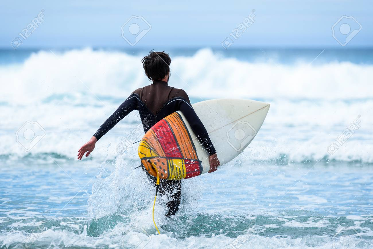 Surfer Guy With Surfboard In Hand Running Towards Big Waves