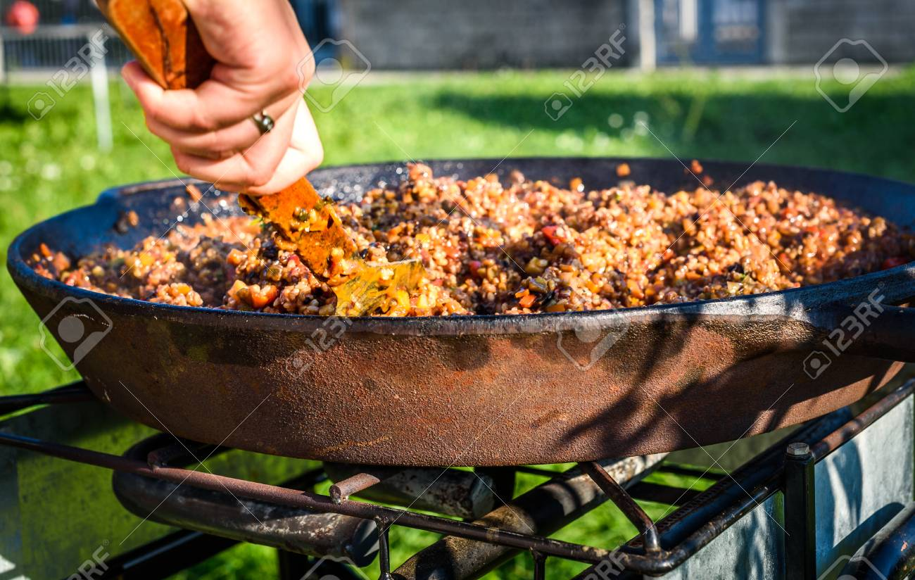 Cooking And Making Traditional Spanish Paella In Iron Cast Pan