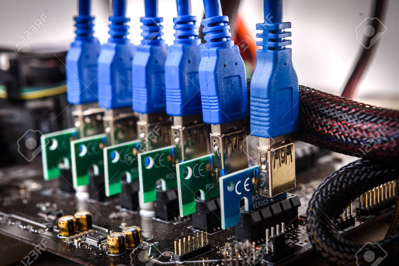 Cryptocurrency mining rig PCIe riser extenders plugged to motherboard