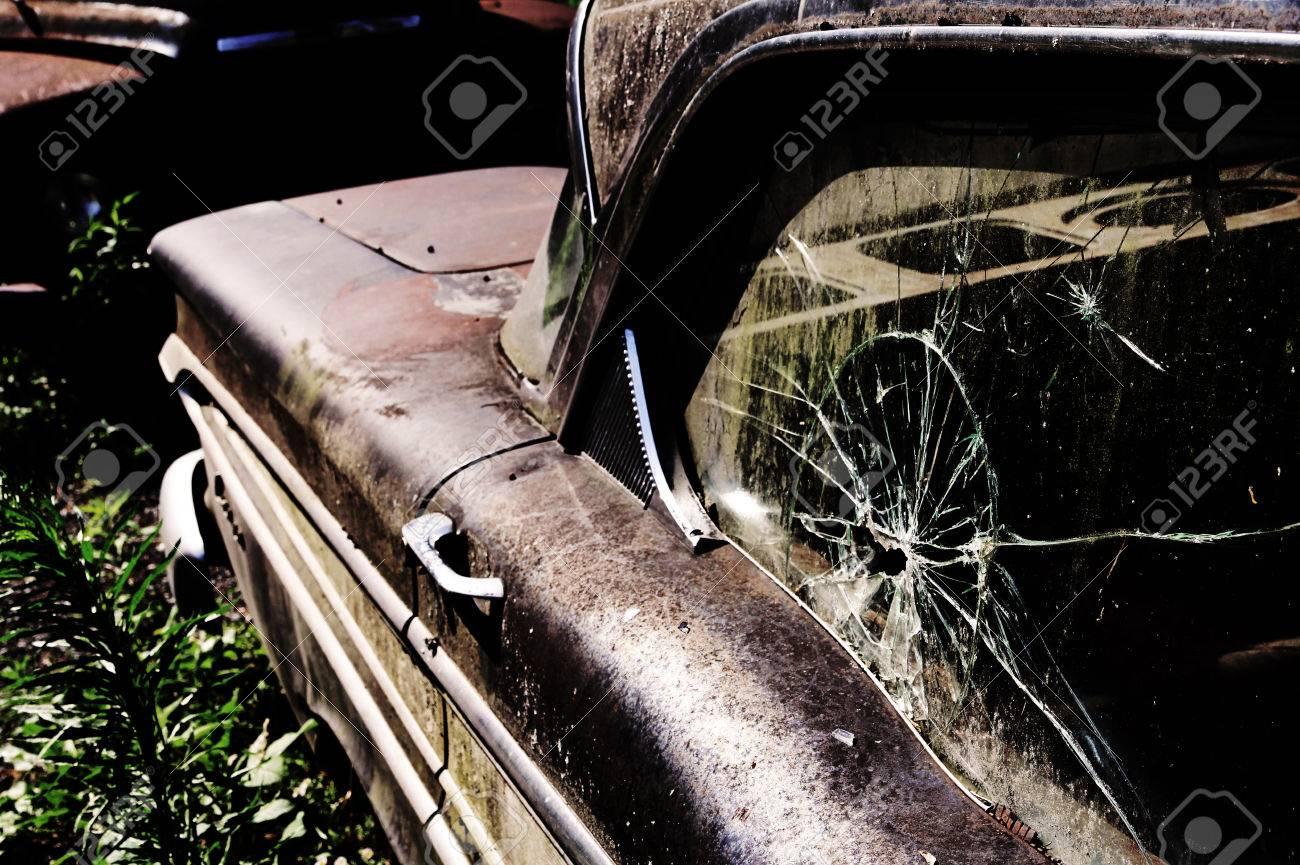 A broken side window in an old rusted car. A broken vintage - 43543873