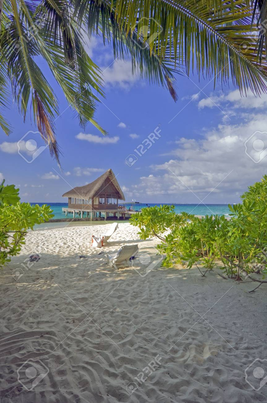 Two empty deck chairs on beach; group of unrecognizable people departing from jetty seen on backround Stock Photo - 3090868