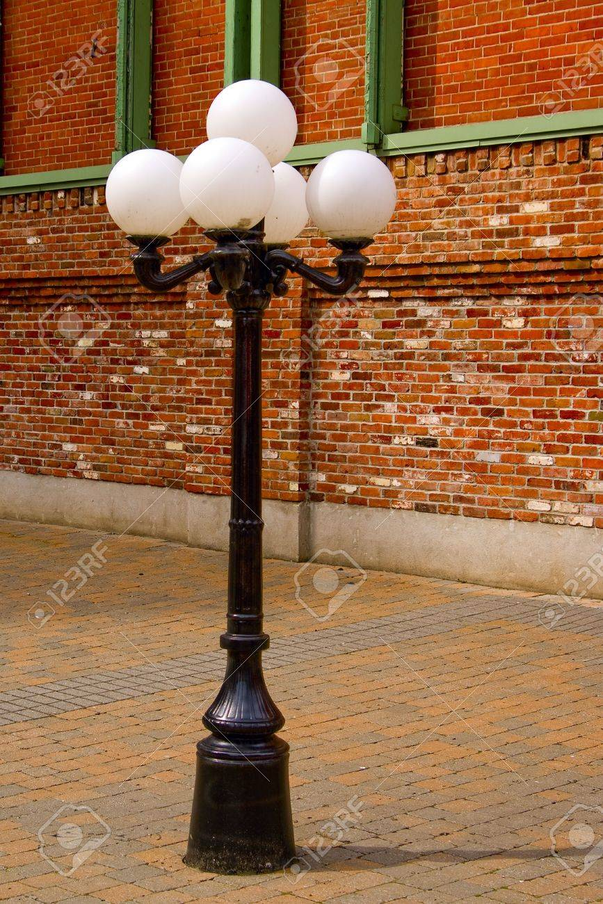 An old-fashioned metal street lamp surrounded by red brick. Stock Photo - 6661042