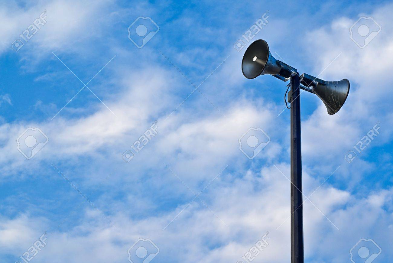 A pair of loudspeaker megaphones mounted atop a tall pole set against a cloudy blue sky. - 7403014