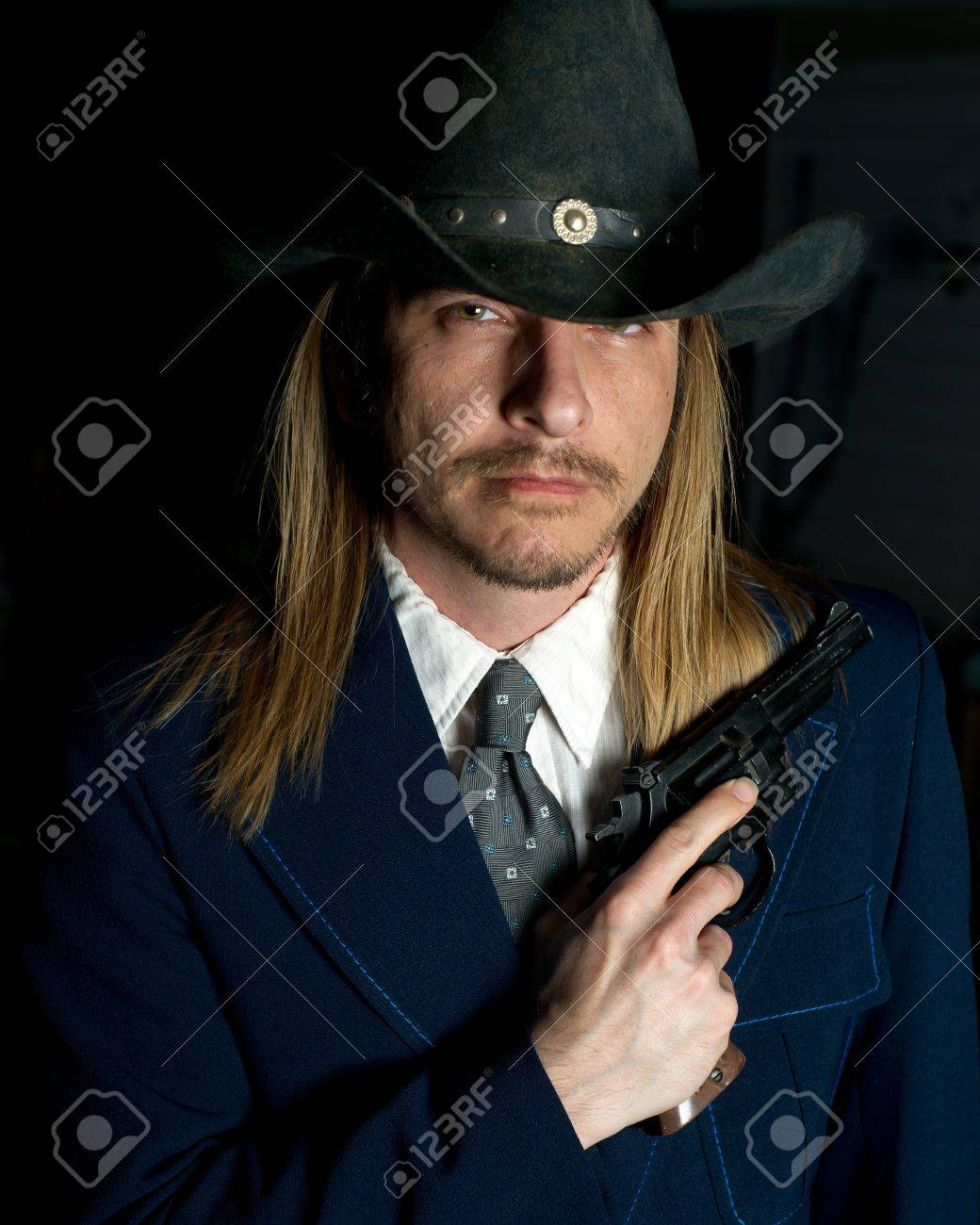 84d6dec1bff31 A long haired man in cowboy hat holds a revolver. Stock Photo - 9572056