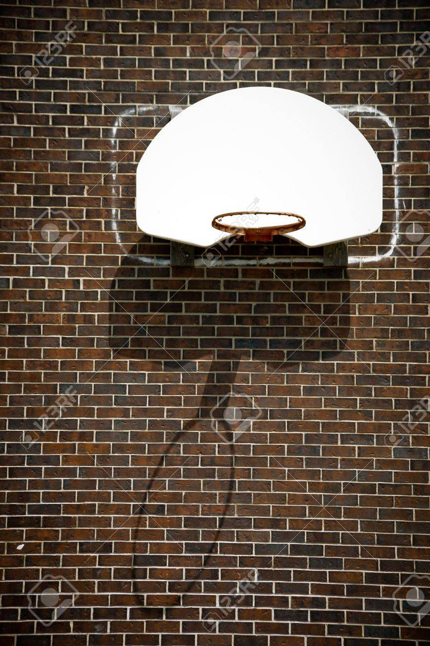 A basketball hoop with no net and white backboard affixed to a brown, brick wall. - 11018707
