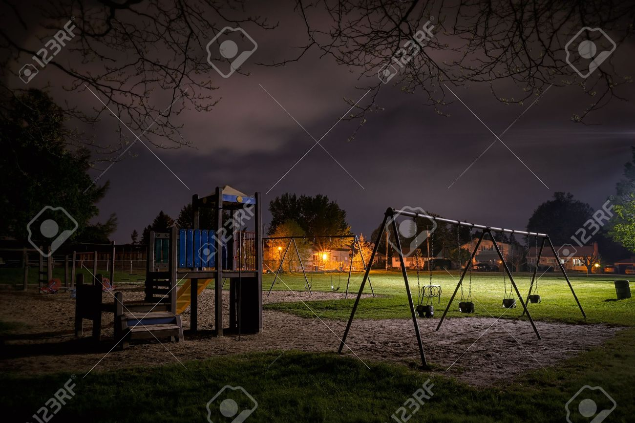 A creepy scene of a deserted children's playground in a suburban park at night time. - 19663729