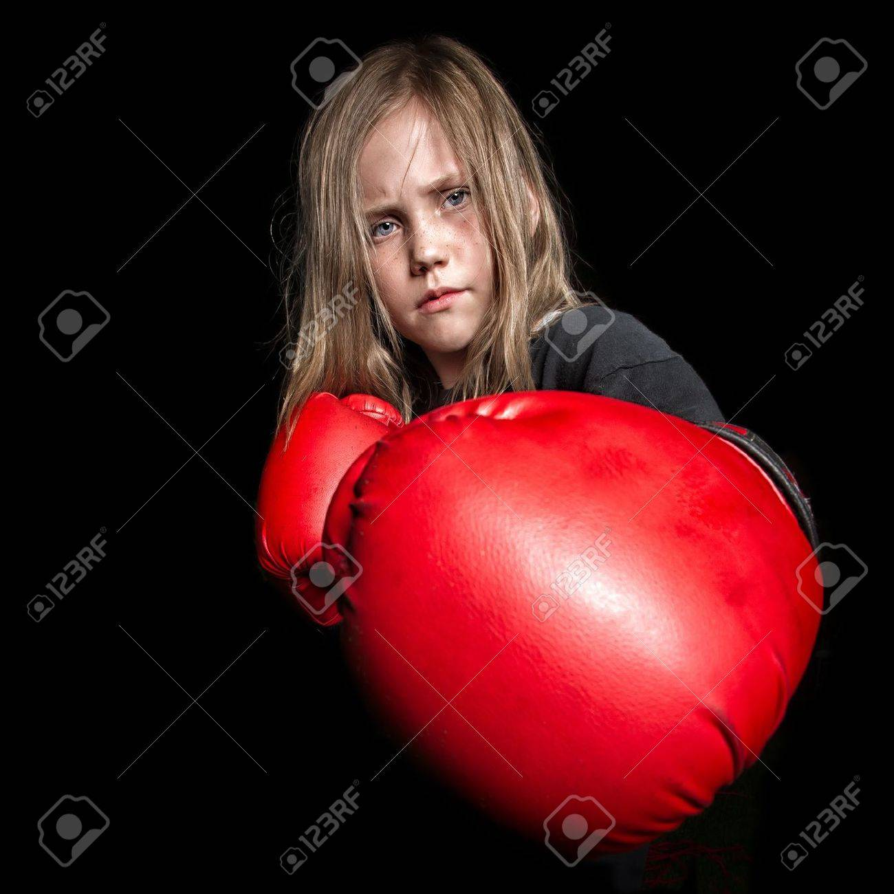 A young female child looks mean as she gets ready to throw a punch at the camera wearing boxing gloves - 21284958