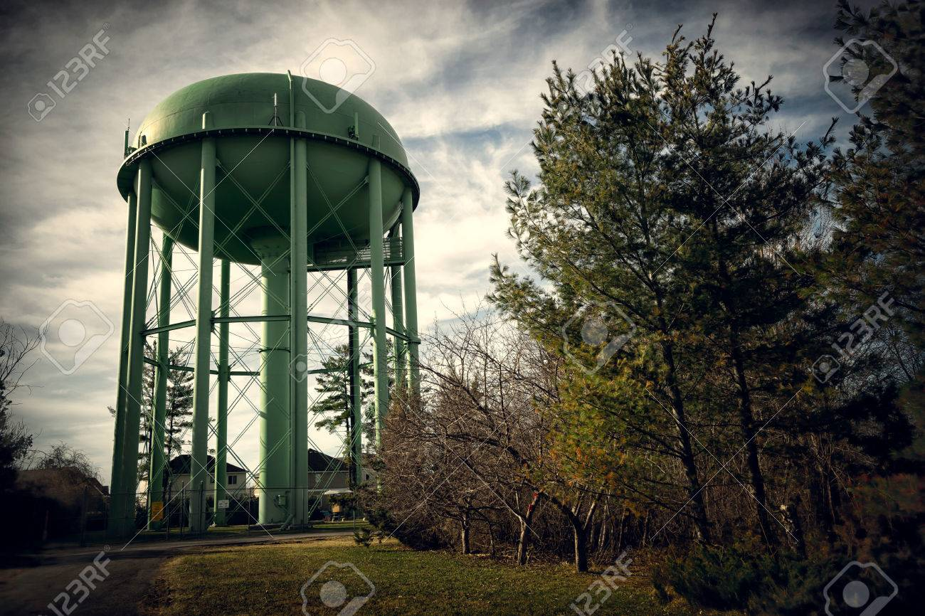 An old antique style tall green water tower or water storage tank standing high above & An Old Antique Style Tall Green Water Tower Or Water Storage ...