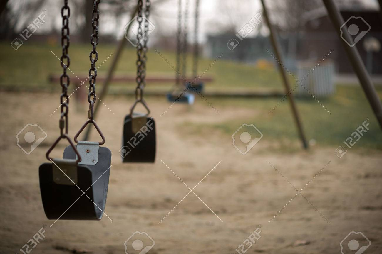 Children's swings hang empty an idle at a playground on a dull, overcast day. - 39375883