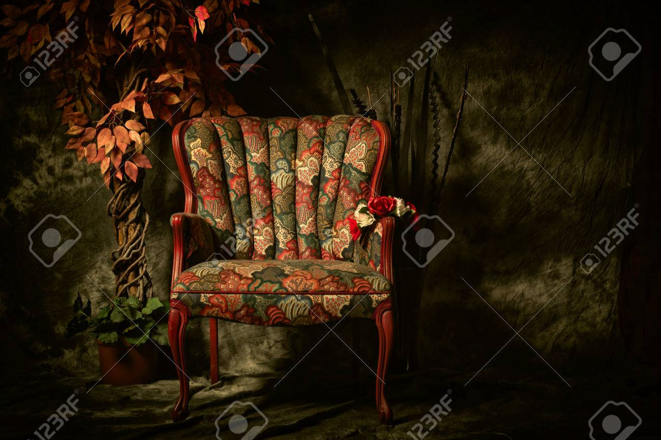 an empty antique patterned chair shot in a chiaroscuro lighting
