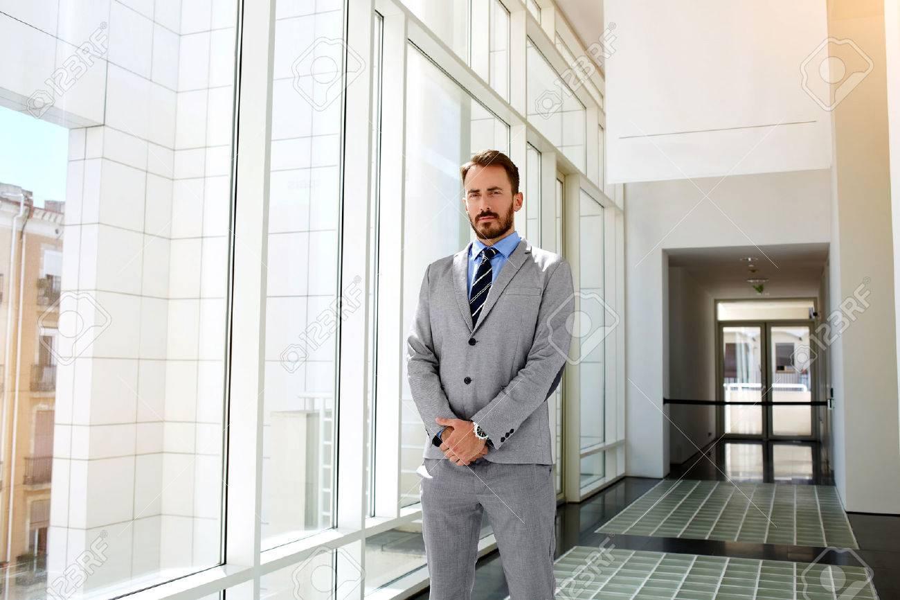 Abbigliamento Ufficio Uomo : Giovane uomo orgoglioso amministratore delegato vestito in tuta di