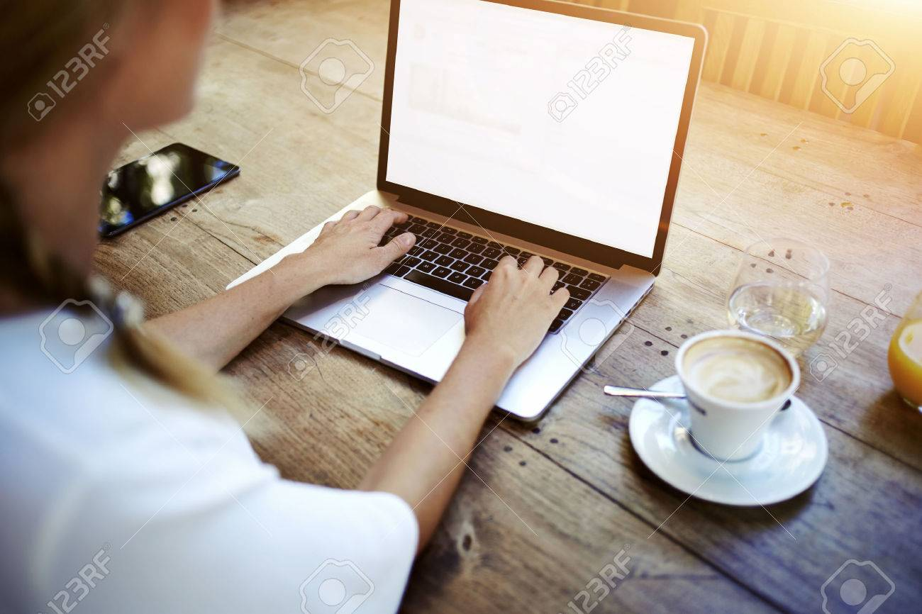 Cropped image of a woman's hands keyboarding on net-book while sitting at the wooden table in cafe, female student working on laptop computer with copy space screen background for your text message - 56368630