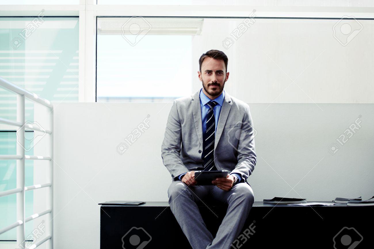 Jeune avocat homme de vêtements de cérémonie assis avec tablette
