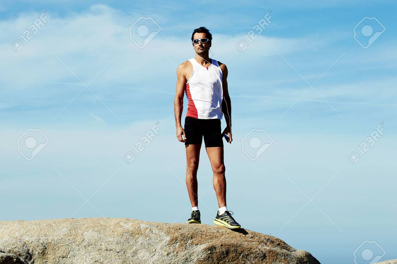 Full length portrait of mature sports man in workout wear standing on the hill of mountain rock while taking break after active fitness training, adult male runner resting after workout outdoors - 58106650
