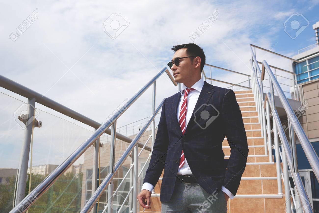 retrato de un exitoso hombre asitico elegante vestidos con ropa elegante de pie en la calle