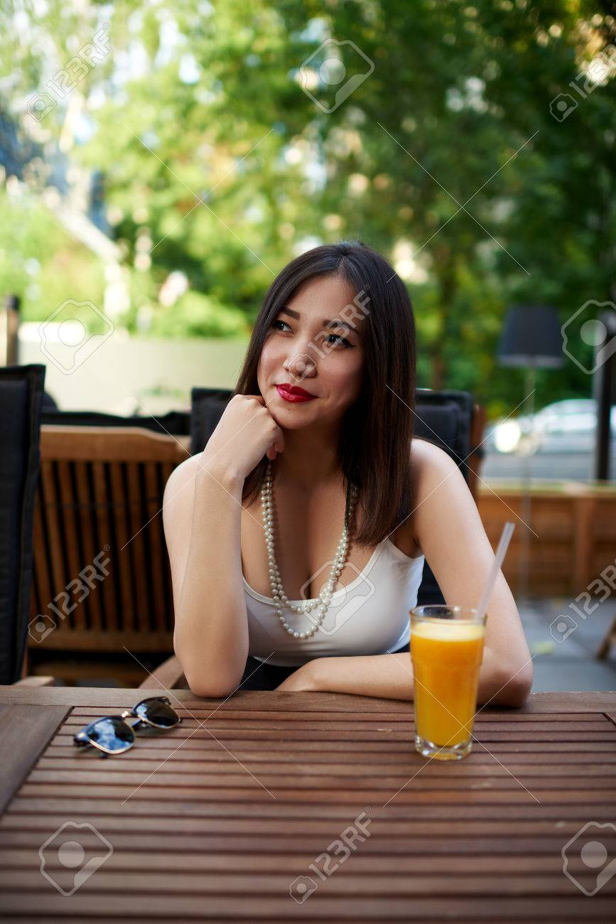 Portrait Of Cute Asian Woman Sitting Alone At Modern Coffee Shop Terrace In  The Summer Day