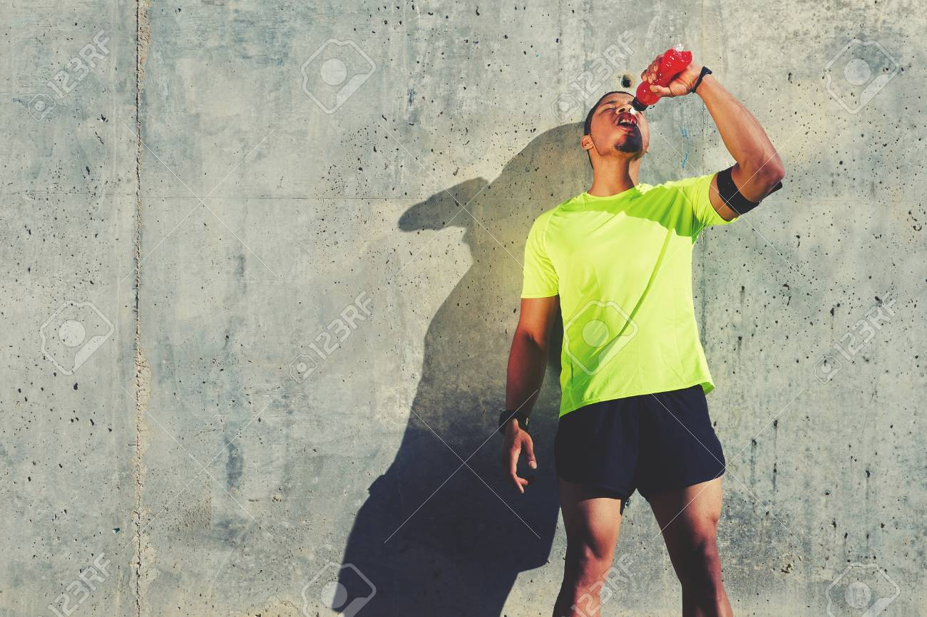 Young tired athlete refreshing with energy drink while standing against cement wall background with copy space area for your text message or content, male runner resting after exercise outdoors - 58048388