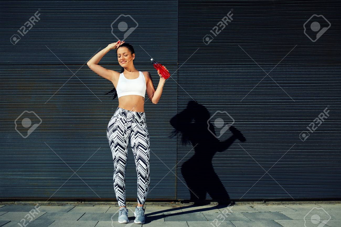 Happy female runner hold water bottle while standing against black wall background with space for your text message,athletic woman refreshing with energy drink during fitness training outdoors in city - 56580309