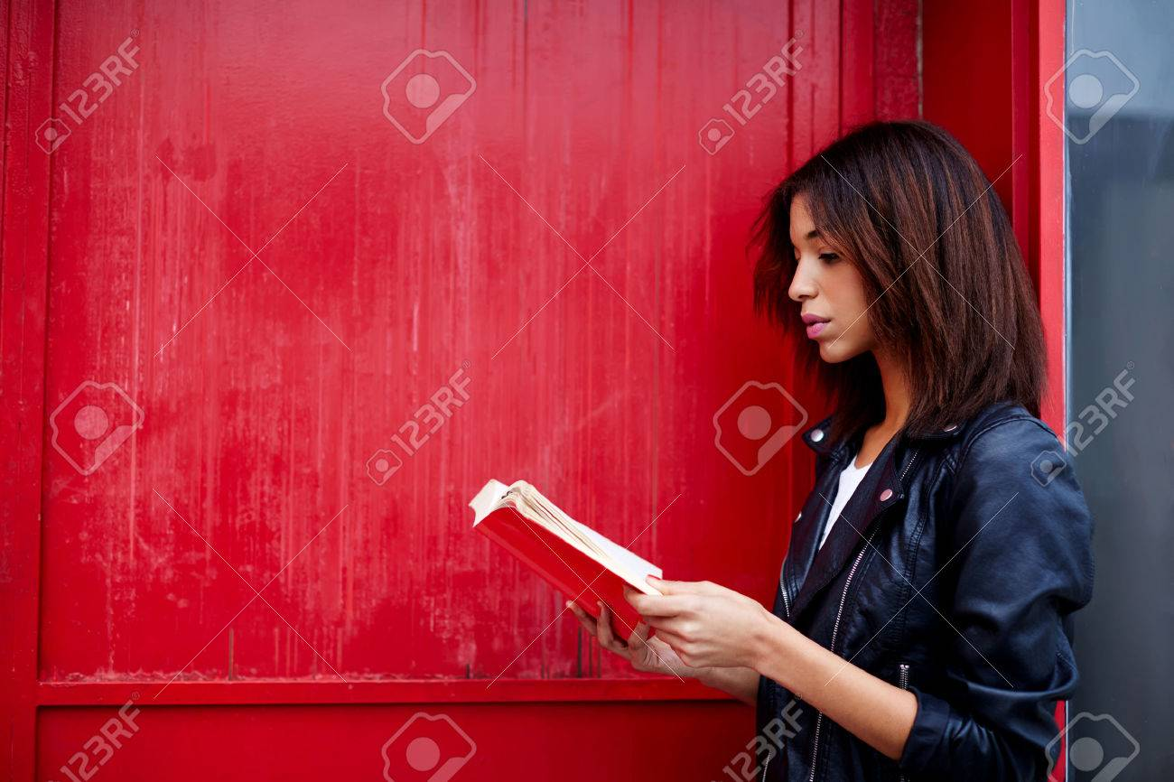 Young female student reading interesting book while standing in the city on red wall background with copy space for your text message, afro american woman read literature while standing outdoors - 58051258