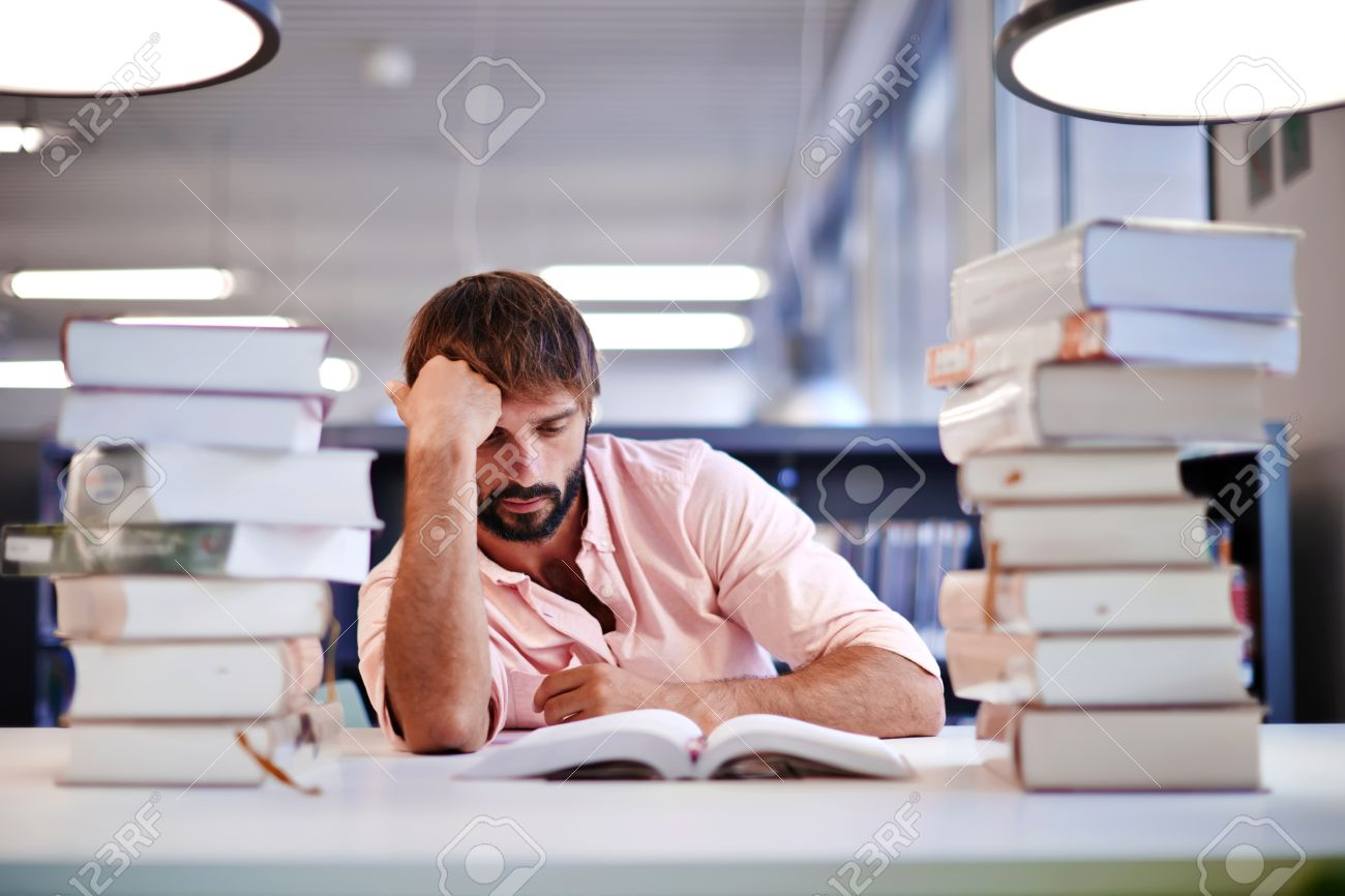 Frustrated Male Student Sitting At The Desk With A Huge Pile ...
