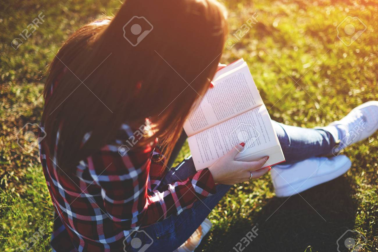 Pretty relaxed young woman reading a book at the lawn with sun shining - 56910067