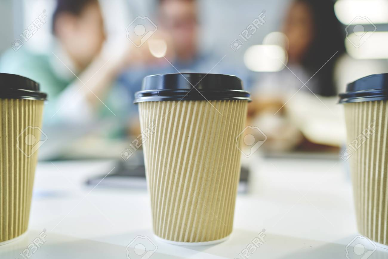 Selective focus on three disposable cardboard cups with coffee