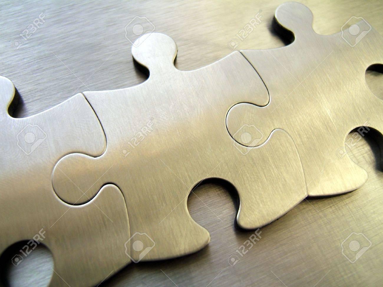 Three metallic jigsaw pieces on a steel background Stock Photo - 294879