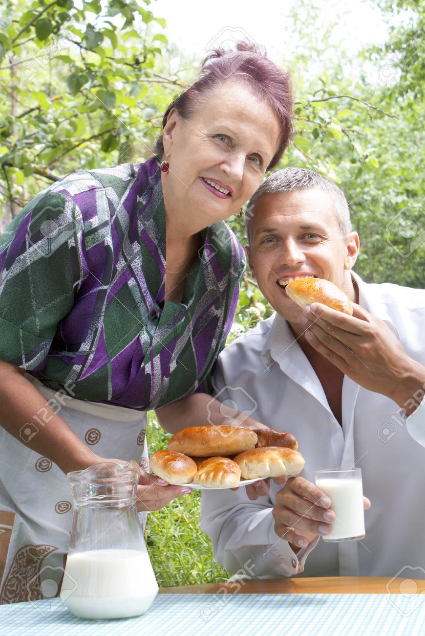 The happy family eats baked house pies with fresh milk in a summer garden Stock Photo - 14232926