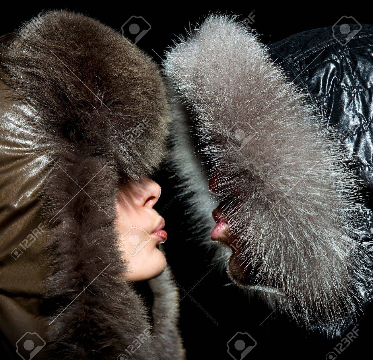 Kiss in the winter of men and women in fur hoods Stock Photo - 19226690