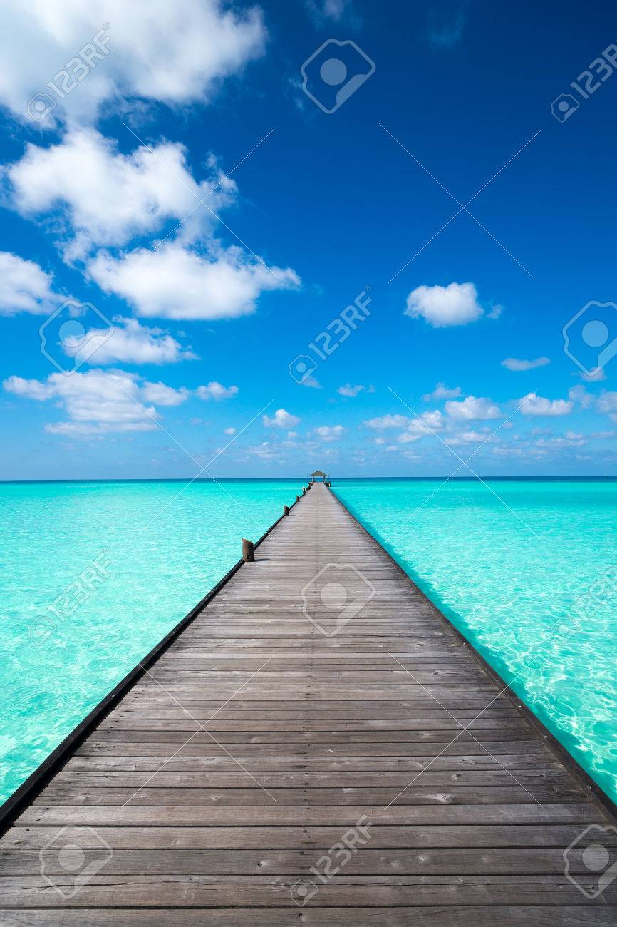 Wooden pier with blue sea and sky background - 44232839