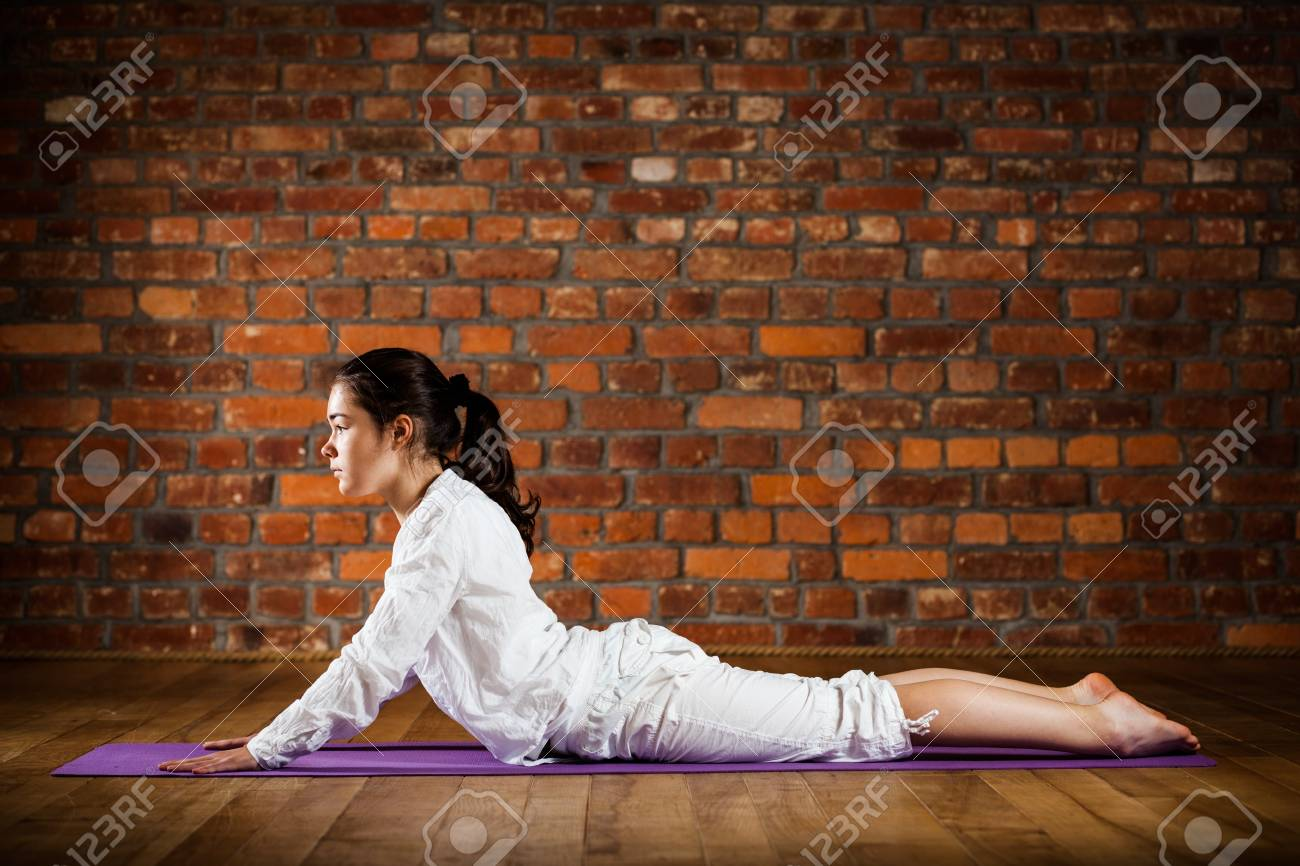 Woman exercising yoga against brick wall Stock Photo - 17993509