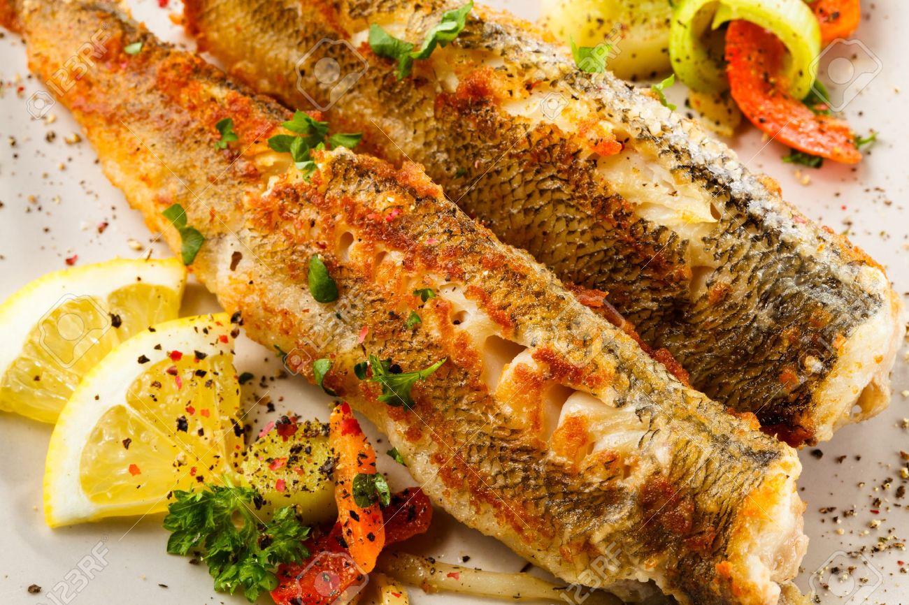 Fish dish - fried fish and vegetable salad - 18971138