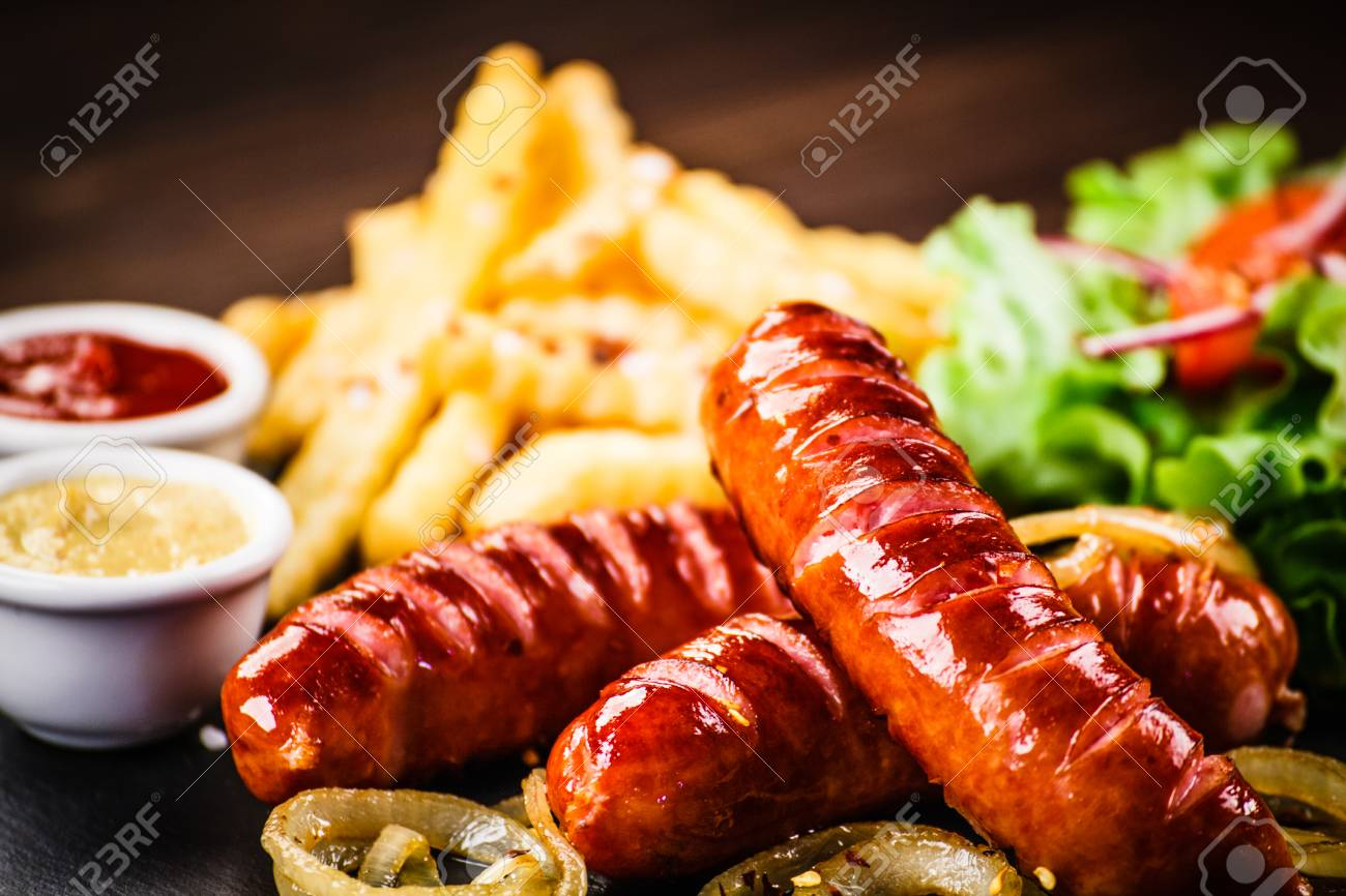 Grilled sausages, French fries and vegetables - 102458615