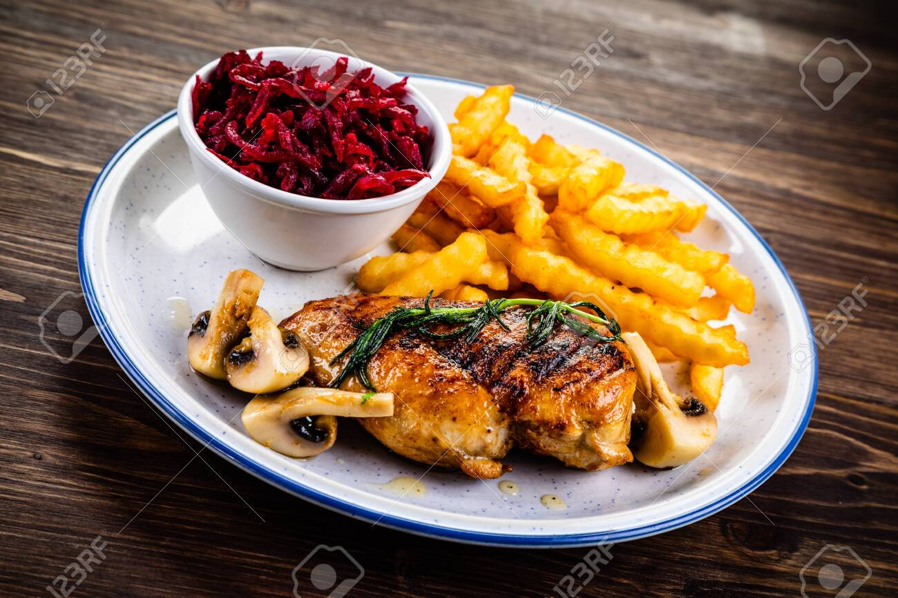 Grilled chicken fillet with french fries and vegetables - 124264285