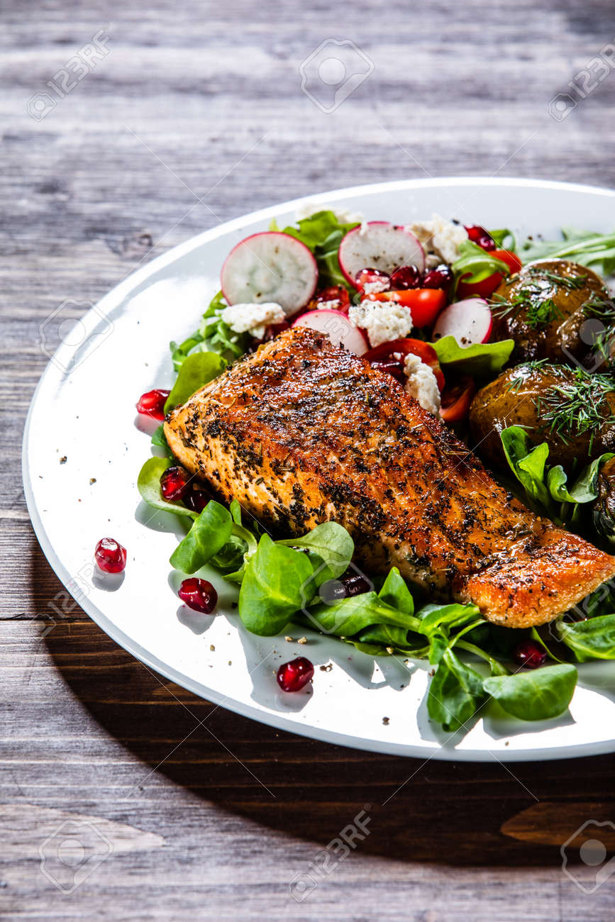 Grilled salmon, baked potatoes and vegetable salad - 130569150