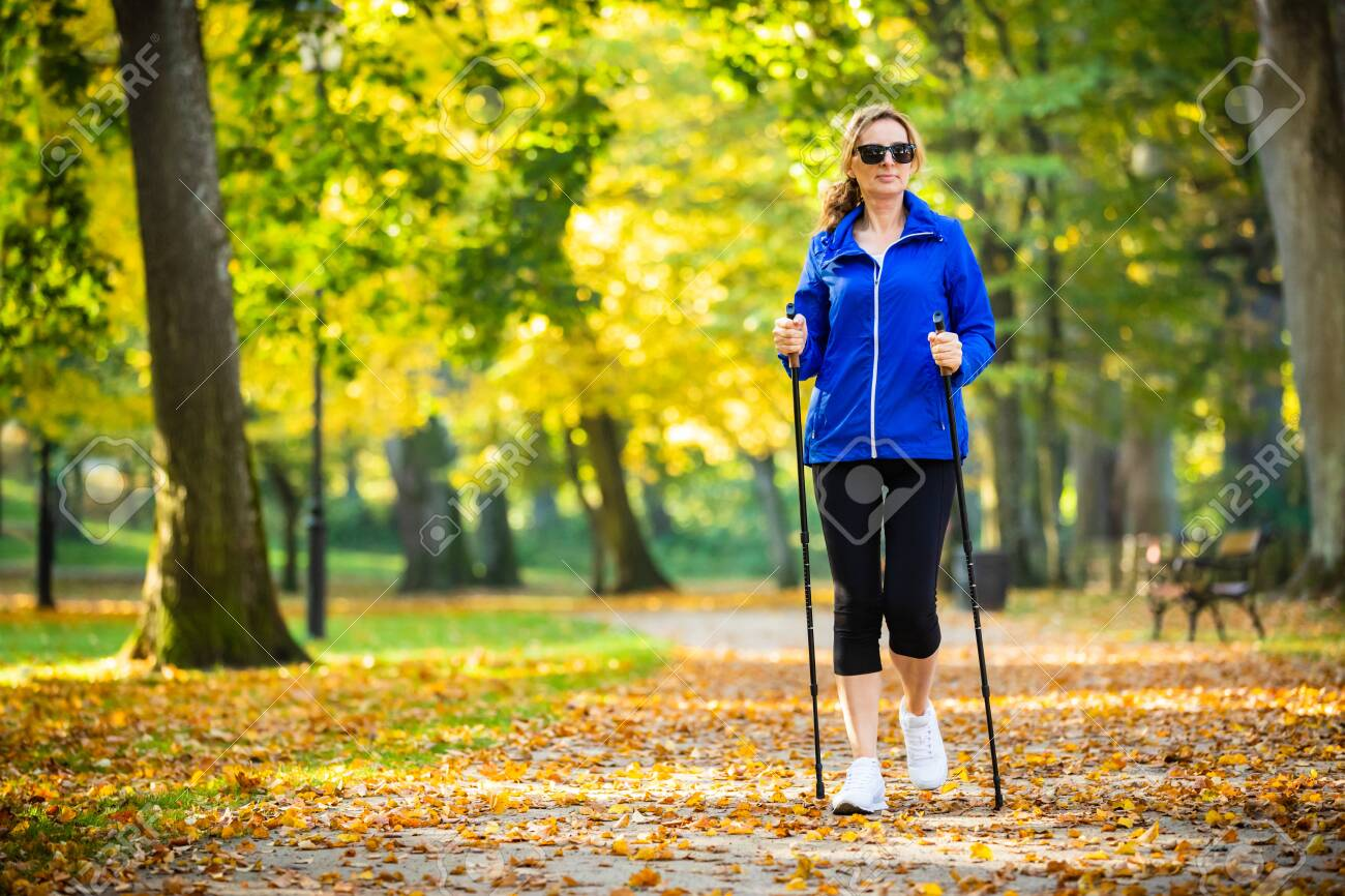 Nordic walking - middle-age woman working out in city park - 135882182