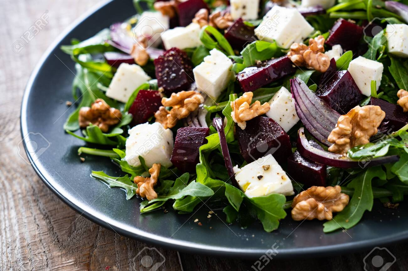 Beetroot salad with goat cheese on wooden background - 144567485