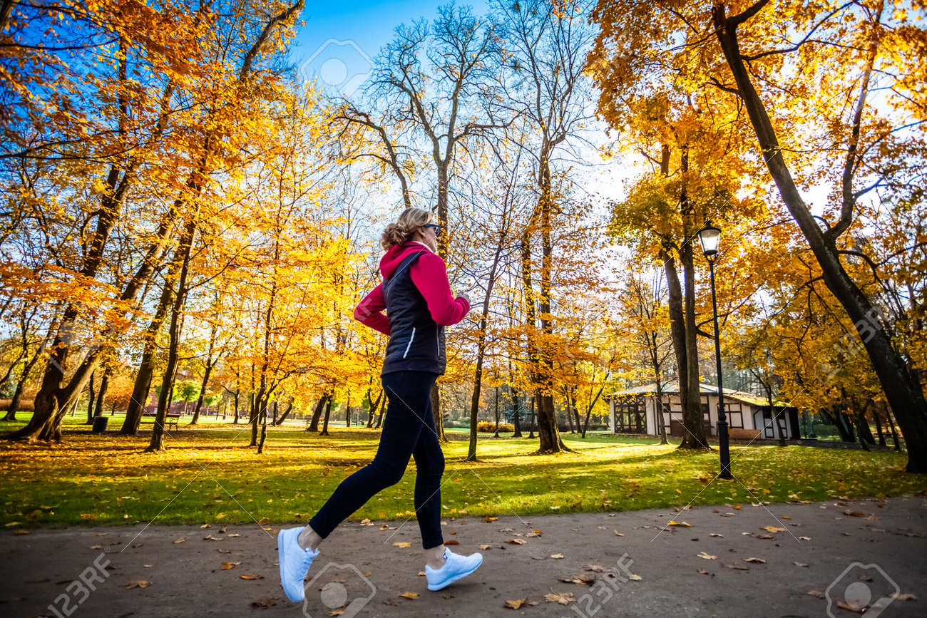 Healthy lifestyle - woman running in city park - 147993949
