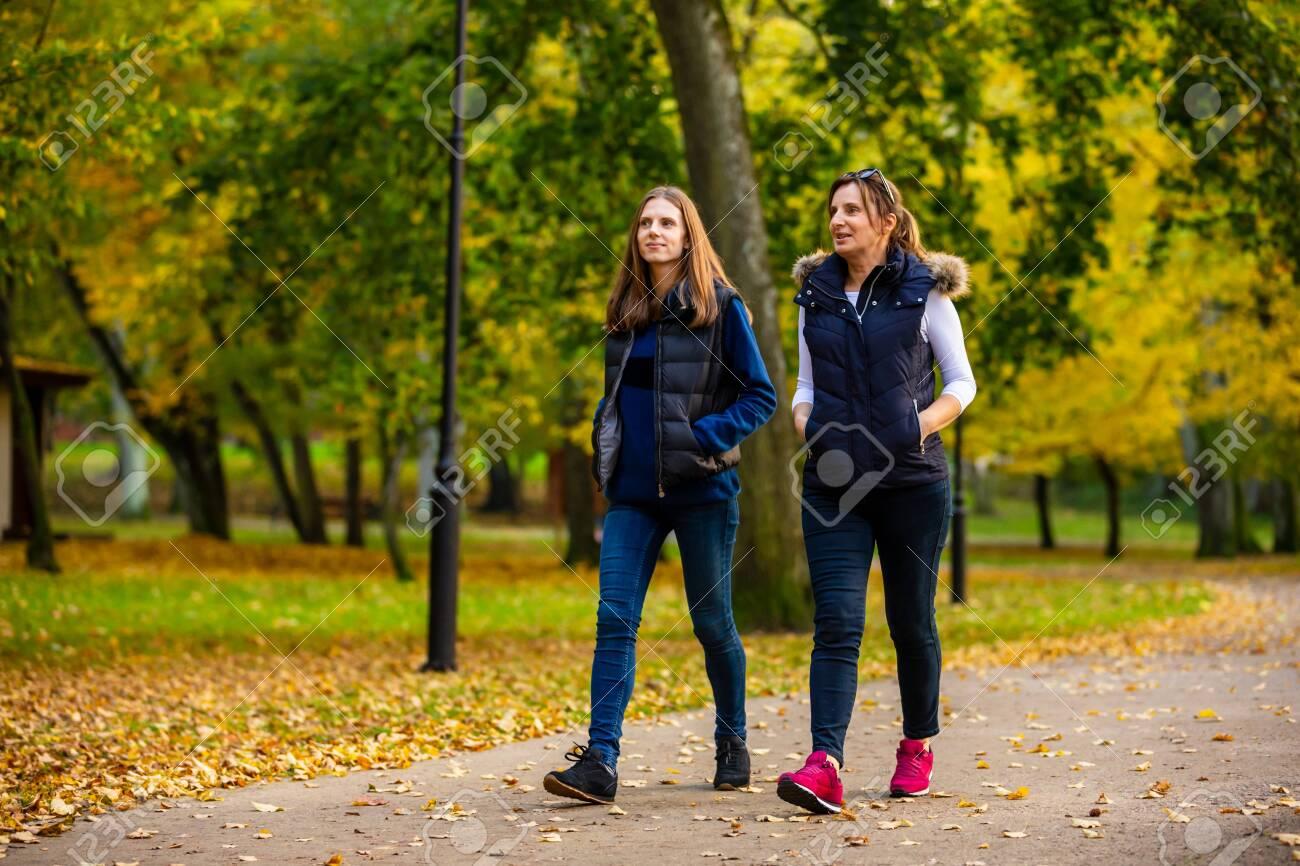 Two women walking in city park - 148095422