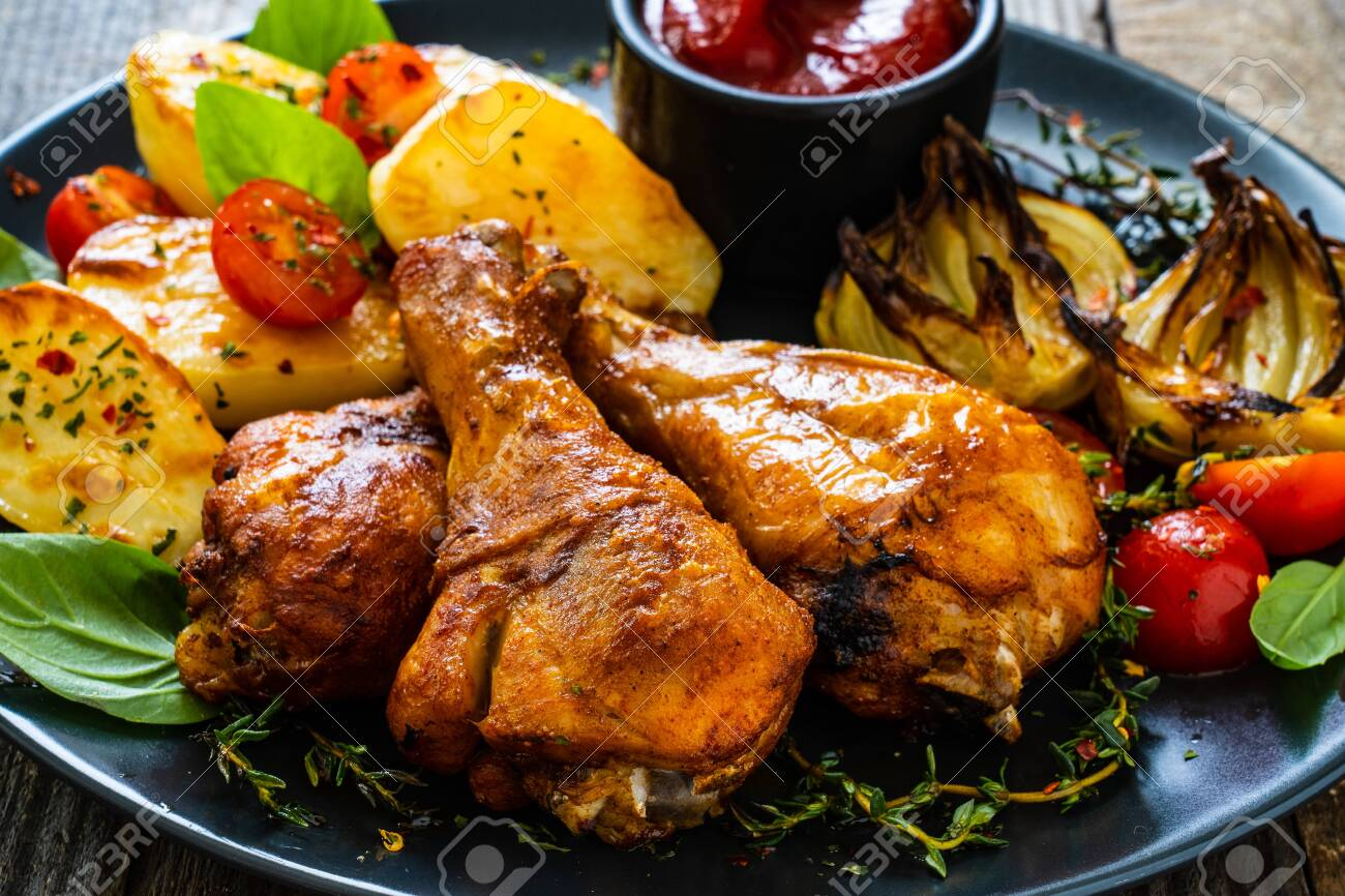 Barbecue chicken drumsticks with vegetables on wooden table - 149290178