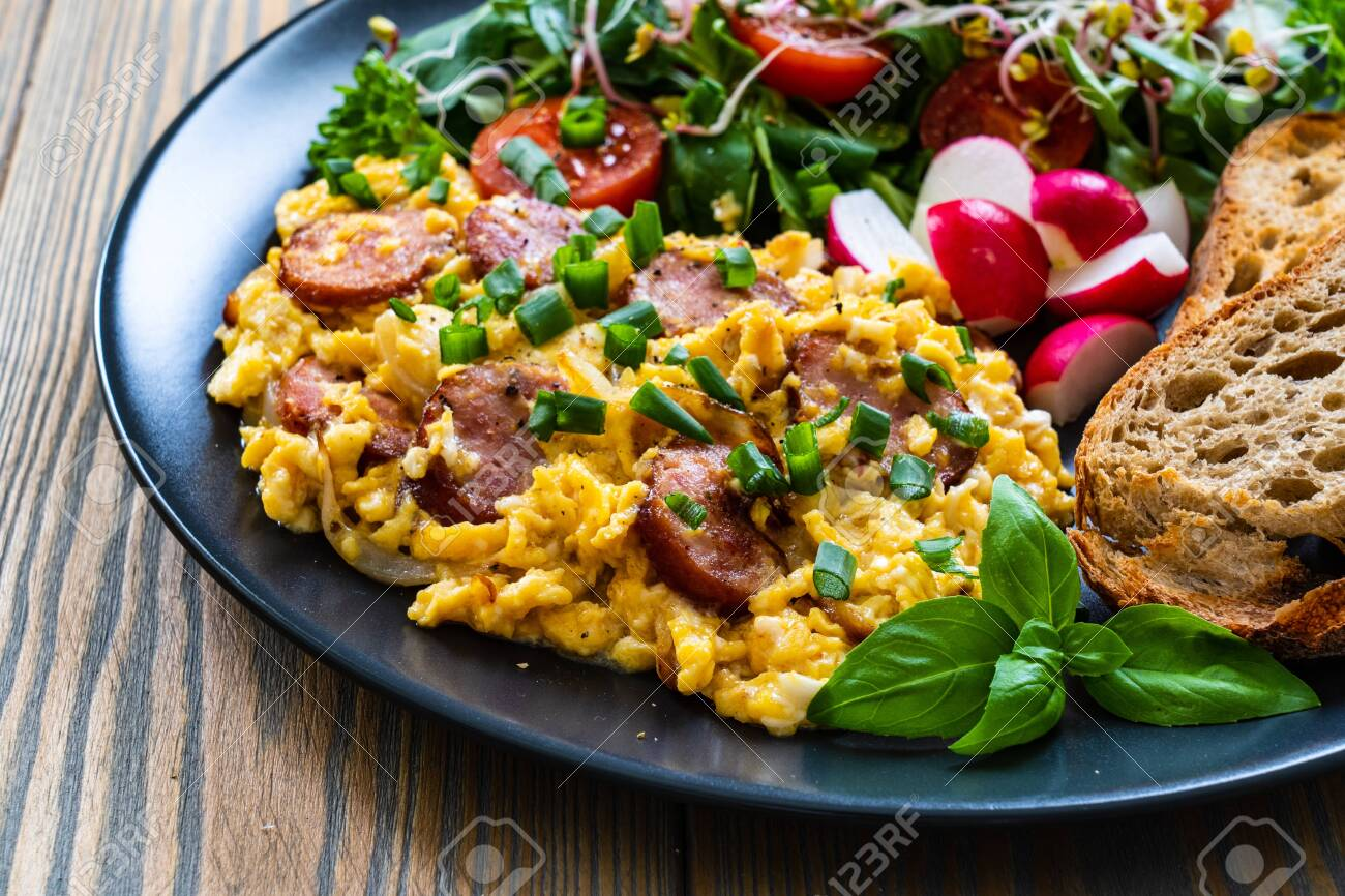 Delicious breakfast - scrambled eggs with fried sausages, vegetable salad and toasted bread served on black plate on wooden table - 150169797