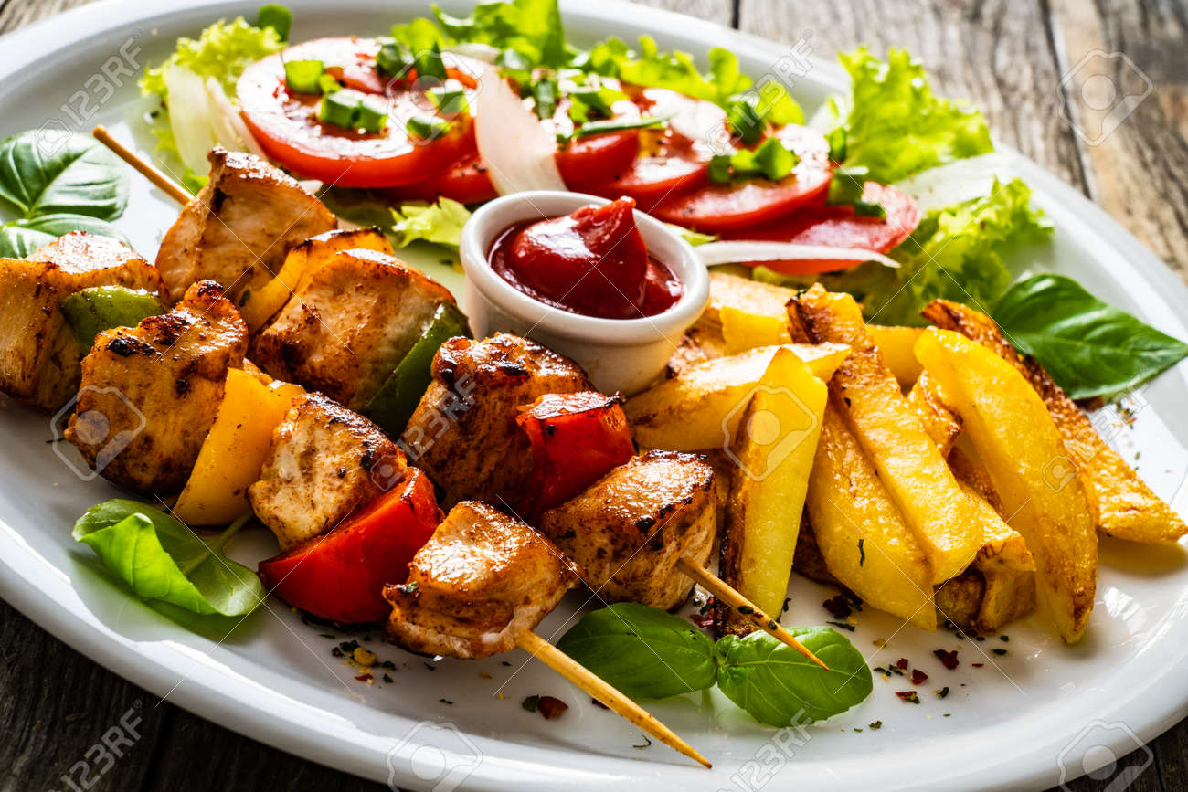 Skewers - grilled meat with French fries and fresh vegetables on wooden background - 155743128