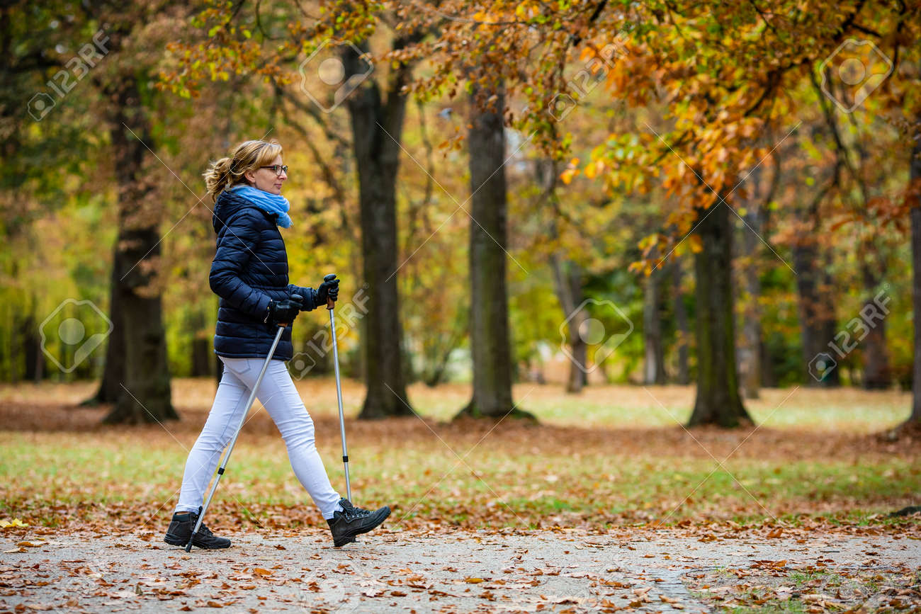 Nordic walking - middle-age woman training in city park - 156549380