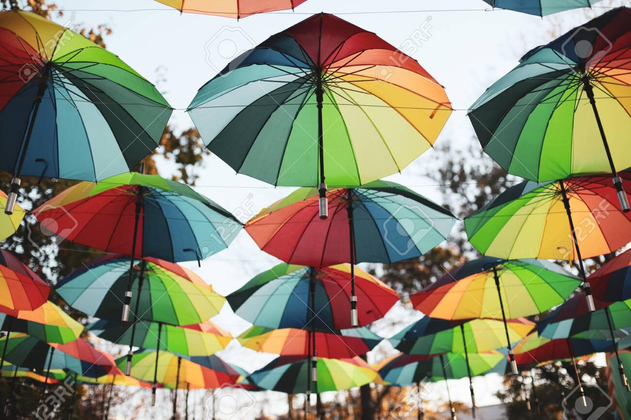 Rainbow colored umbrellas hang in a public park - 133307574