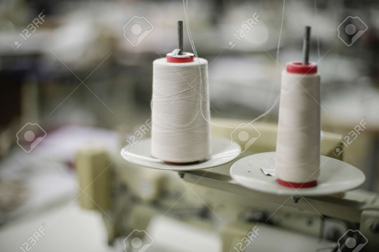 Shallow depth of field (selective focus) image with thread spools in a textile factory. - 166661758